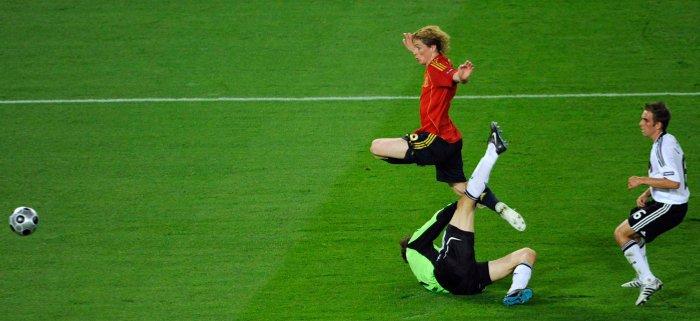 Fernando Torres se adelanta a Lahm y pica superando a Lehmann para lograr el gol español. / Reuters