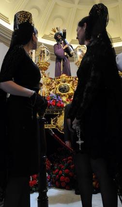 Dos jóvenes de mantilla observan al Señor del Gran Poder.  Foto: Juan Carlos Vázquez