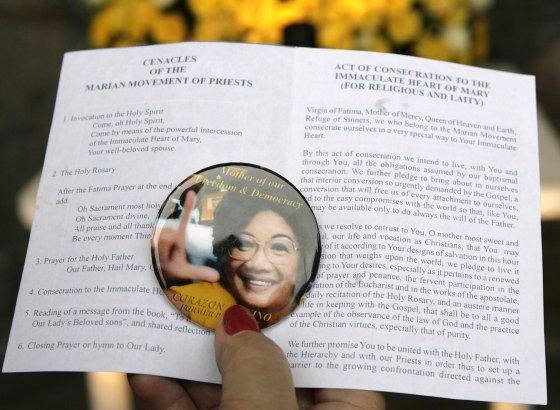 Una foto de Aquino sobre una octavilla de oraciones religiosas. / AFP Photo · Reuters