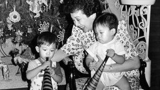 Corazón Aquino juega con uno de sus hijos, Justin (i), y otro niño. / AFP Photo · Reuters