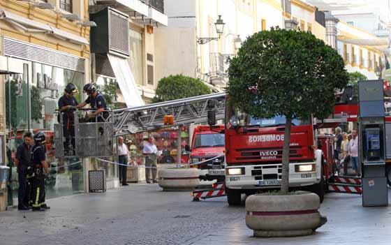 Dos bomberos esperan abajo para relevar a los que bajan de la grúa.  Foto: Belén Vargas