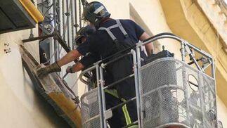 Los bomberos intentan desprender el balcón.  Foto: Belén Vargas