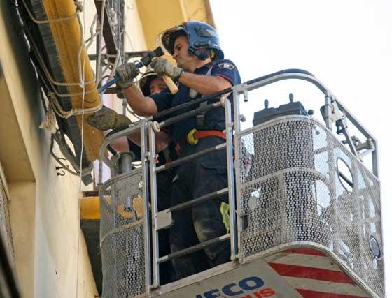 Los bomberos utilizan un cincel y un martillo para extraer el balcón.  Foto: Belén Vargas