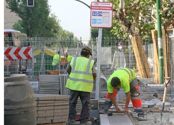 Obreros colocan el pavimento del carril bici junto a una parada de autobús./ Belén Vargas