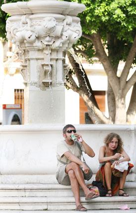 Una pareja descansa a la sombra mientras toma un refresco para sofocar la calor.  Foto: Victoria Hidalgo/Juan Carlos Vázquez