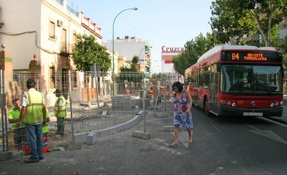Una mujer cruza por la calzada junto a la valla que la separa del acerado por las obras./ Belén Vargas