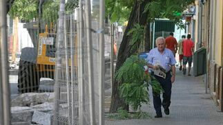 Un hombre pasea junto al vallado que separa la acera de las obras del carril bici./ Belén Vargas