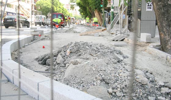 Coches circulan por la Avenida de Luis Montoto junto a los obreros que trabajan en la ampliación del carril bici./ Victoria Hidalgo