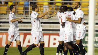 Los jugadores del Sevilla felicitan a Adriano tras el primer gol.   Foto: Cristina Quicler (Afp)