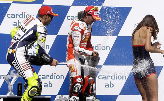 Valentino Rossi y Toni Elías rocían con champán a una de las azafatas en el podio de MotoGP.  Foto: Reuters