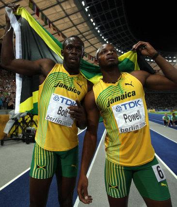 El atleta jamaicano Usain Bolt (i) celebra con su compatriota Asafa Powell (d) su victoria en la final de los 100 metros lisos masculinos de los Mundiales de Atletismo.  Foto: EFE