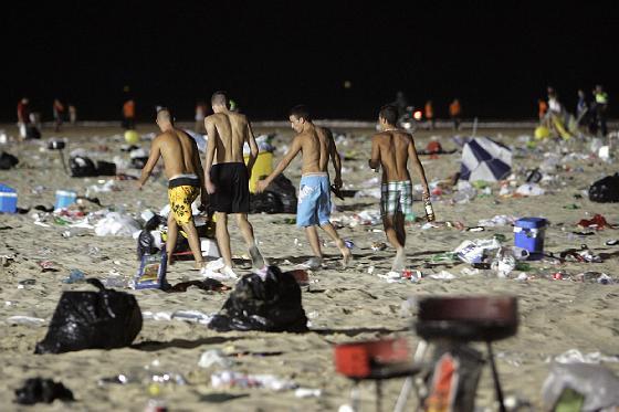 Unos jóvenes abandonan la playa bien entrada la madrugada.   Foto: Lourdes de Vicente