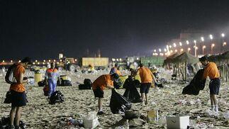 El equipo de limpieza trabaja a destajo para dejar la playa limpia para los primeros bañistas.   Foto: Lourdes de Vicente