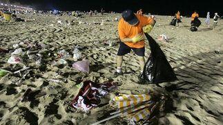 Un operario de limpieza recoge basuras de la arena.   Foto: Lourdes de Vicente