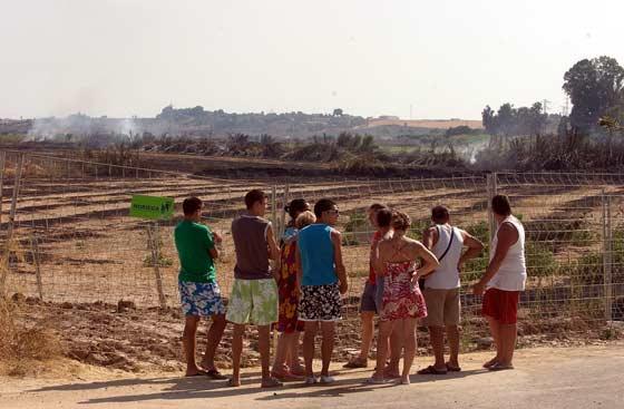Varios vecinos se acercan para observar de primera mano lo ocurrido.  Foto: Manuel Gómez, EFE