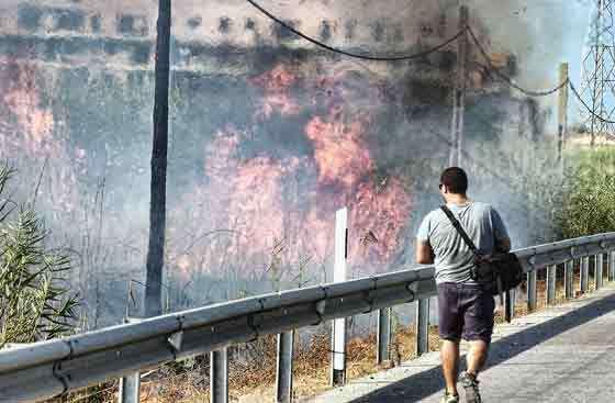 Un hombre observa atentamente el fuego provocado junto a la carretera.  Foto: Manuel Gómez, EFE