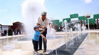 Abuelo y nieto se refresan en la fuente instalada en el Real de la Feria. FOTO: Migue Fernández