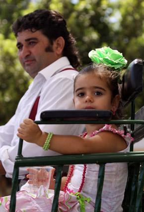 Una niña vestida de flamenca disfruta de su paseo en carro de caballos. FOTO: Migue Fernández