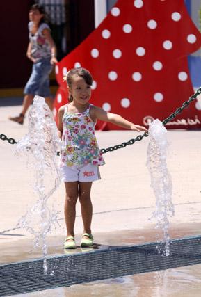 Una niña se resfresca ante el intenso calor en el Cortijo de Torres. FOTO: Migue Fernández