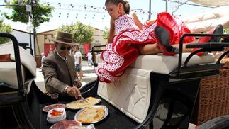 Un carruaje de caballos hace de mesa improvisada para llear el estómago. FOTO:Migue Fernández