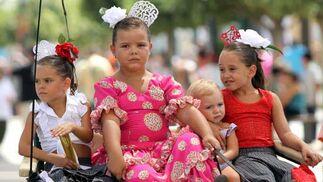 Unas niñas vestidas de flamenca pasean en coche de caballos por el Real./ Migue Fernández