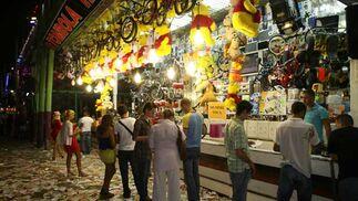 Cientos de papeletas en el suelo de una tómbola y algunos  malagueños probando suerte. FOTO: PUNTO PRESS