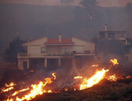 Las llamas rodean una casa en la localidad griega de Anthousa donde el incendio ya ha calcinado decenas de viviendas.  Foto: Efe