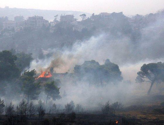 Una casa queda rodeada por las llamas en la localidad de Drafi a 12 kilómetros de la capital griega.  Foto: Efe