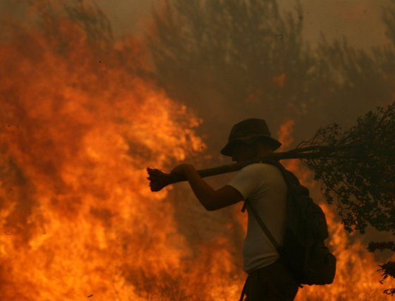 Los voluntarios y bomberos luchan contra el incendio forestal mientras 15.000 personas ya han abandonado sus casas en la zona.  Foto: Efe