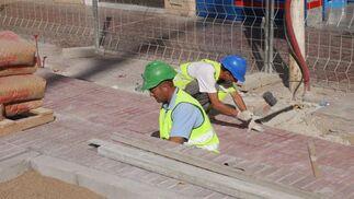 Dos obreros colocan el suelo de la zona exterior de las obras de la estación del Metro./ Jose Ángel García