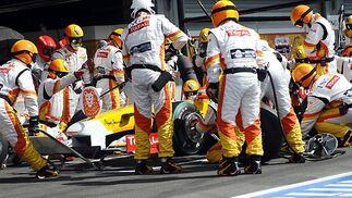 Los mecánicos de Renault trabajan en el tapacubos dañado del coche de Alonso que, a la postre, obligaría al asturiano a abandonar la carrera.  Foto: Afp Photo / Reuters / Efe
