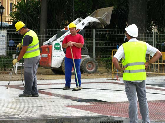 Varios trabajadores limpian el acerado ensuciado por las obras.  Foto: Manuel Gómez