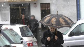 Una señora mayor porta un paraguas para refugiarse de la nieve.  Foto: Juan Carlos Muñoz, Manuel Gómez, Antonio Pizarro