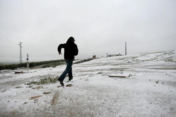 Un hombre se divierte por la nieve en Gerena.  Foto: Juan Carlos Muñoz, Manuel Gómez, Antonio Pizarro