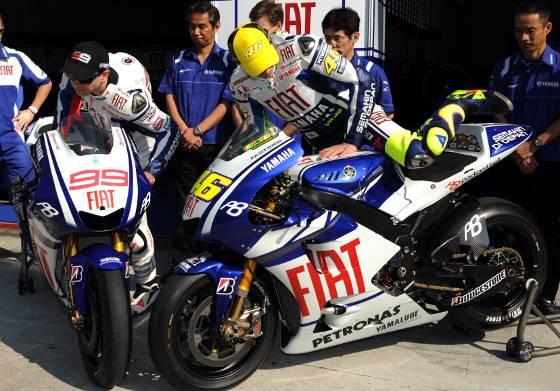 El piloto italiano Valentino Rossi (d) y el español Jorge Lorenzo (i) proceden a montarse a sus nuevas monturas.  Foto: Agencias