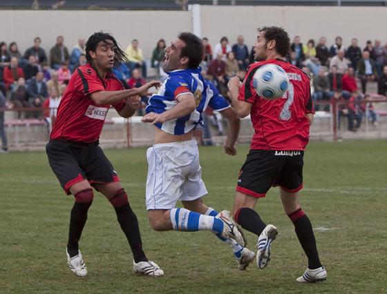 Dani Carrasco salta dentro del área entre dos defensas y pide penalti.  Foto: LOF