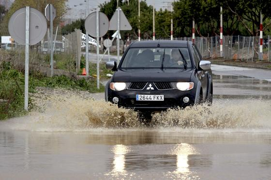 Un vehículo circula por una carretera anegada.  Foto: Migue Fernández, Sergio Camacho, Agencias