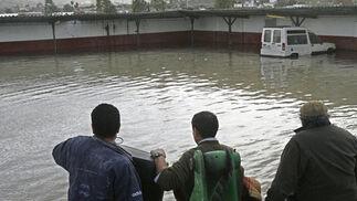 Unos vecinos de Las Pachecas observan los resultados de la riada.  Foto: Pascual