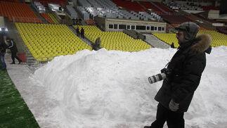 Un fotógrafo delante del montón de nieve amontonada en el estadio.  Foto: Antonio Pizarro