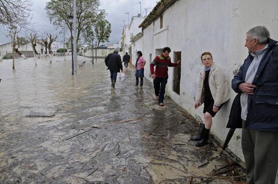 Habitantes de Lora del Río andan sobre los restos de los árboles que cubren el agua.  Foto: Juan Carlos Vázquez