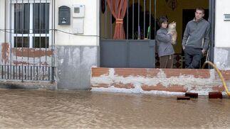 Una familia de Lora del Río asomada a la calle, cubierta totalmente por el agua.  Foto: Agencias