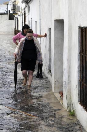 Dos mujeres andan sobre el agua en una calle de Lora del Río.  Foto: Juan Carlos Vázquez