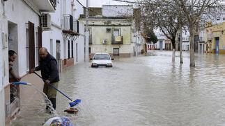 Varios vecinos de Lora del Río usan mangueras y escobas para achicar el agua que inunda sus casas.   Foto: Juan Carlos Vázquez