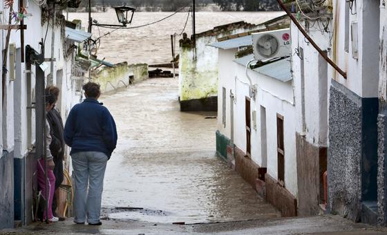 Varios vecinos de Lora del Río miran su calle inundada.  Foto: Agencias