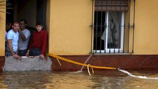 Una familia de Tocina utiliza una manguera para achicar el agua de su casa.  Foto: Agencias