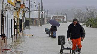 Un hombre achica el agua de su casa con un tubo mientras otros andan por una calle de Tocina.  Foto: Juan Carlos Vázquez