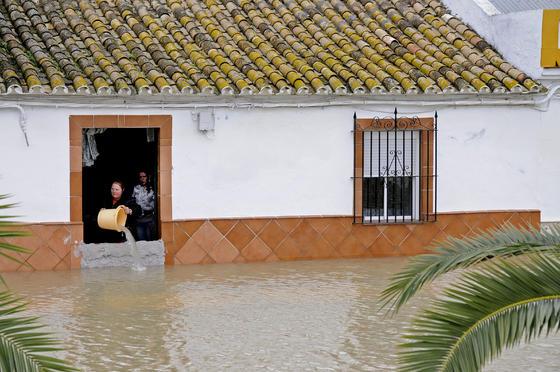 Una mujer achica el agua que inunda su casa con un cubo (Tocina).  Foto: Juan Carlos Vázquez