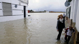 Una mujer y un niño andan sobre el agua que inunda Tocina.  Foto: Juan Carlos Vázquez