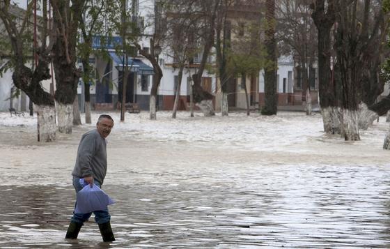 Un hombre sostiene una bolsa y anda sobre el agua que inunda Lora del Río.  Foto: Agencias
