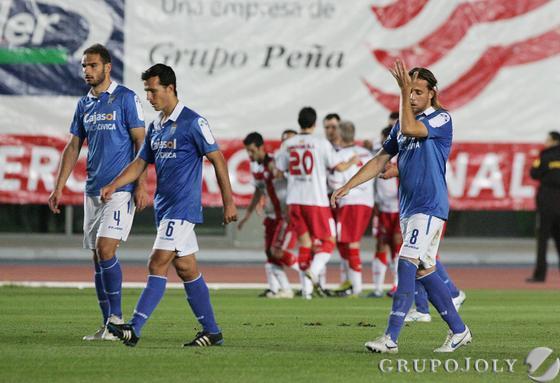 Lombán, Bruno Herrero y Cordero, cabizbajos mientras los jugadores del Huesca celebran el tanto.   Foto: Pascual